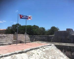 The Cuban flag is at left. A basic web search did not explain the flag on the right. Old Spanish fort just outside Havana.